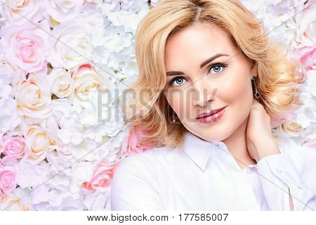 Portrait of a beautiful middle-aged woman over floral background. Spring mood. Summer fashion. Natural cosmetics, make-up, skincare.
