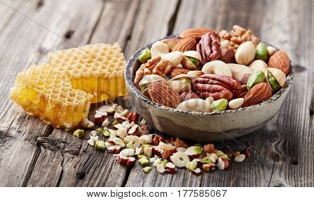Mix nuts with honeycombs on a wooden background.