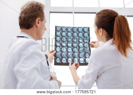 How can I help. Experienced attentive competent neurosurgeon pointing out some issues judging on patients brain scans while discussing the diagnosis with another doctor