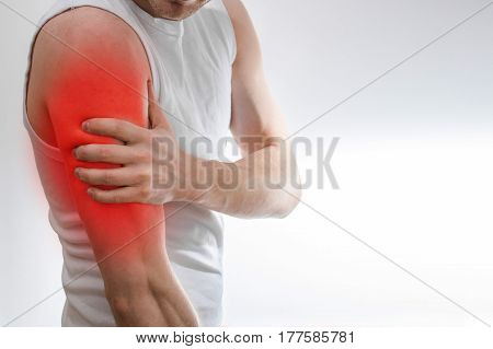 A Man In A White T-shirt Holds On To The Shoulder, Arm,  Wrist, Forearm, Sports Injury, Experiencing