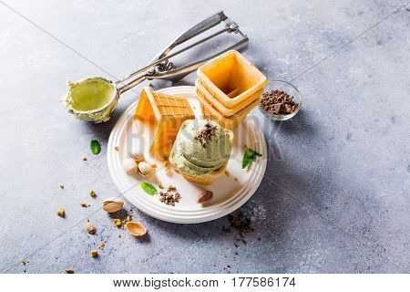 Pistachio ice cream in waffle cups on gray stone background. Homemade summer food concept with copy space. High angle view.
