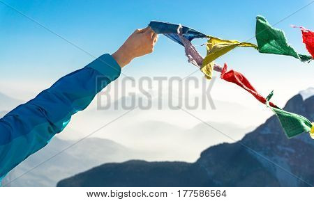 Happy celebrating winning success female hand holds colored flags with elated arm raised up high in celebration of having reached mountain top. Holding tibetan prayer flags blowing in the wind. Reaching summit goal during hiking travel trek.