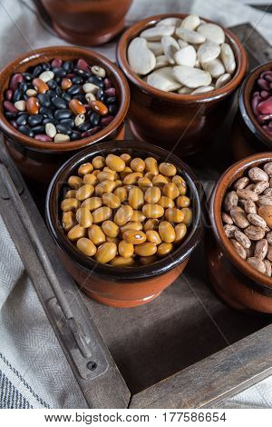 Assortment of beans on black wooden background. Soybean red kidney bean black beanwhite bean red bean and brown pinto beans
