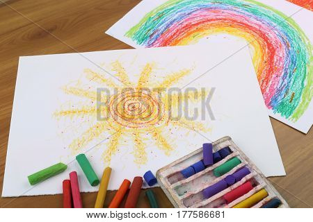 Drawing with pastel crayon. Crayon pieces and drawings on table. Hand drawn sun and rainbow.