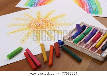 Drawing with pastel crayon. Crayon pieces and drawings on table. Hand drawn sun.