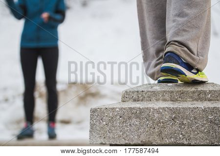 Legs of teenagers at parkour training - sneakers in winter park, horizontal