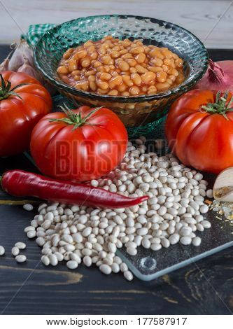Traditional English food - baked white beans in tomato sauce and ingredients ready to cook - tomatoes dried white beans and onion chili pepper