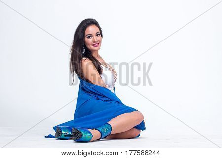 Pretty woman posing in white swimwear and blue bathrobe.