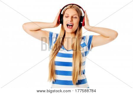 Young woman with headphones listening and singing to music, isolated on white