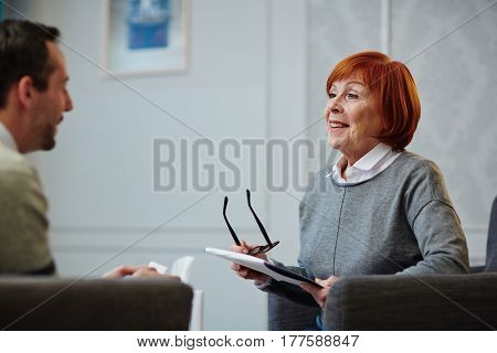 Cheerful mature psychologist with clipboard in hands sitting opposite her male patient and looking at him with smile during therapy session