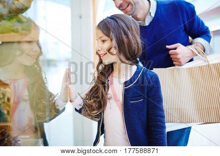 Smiling girl looking at shop-display at something curious