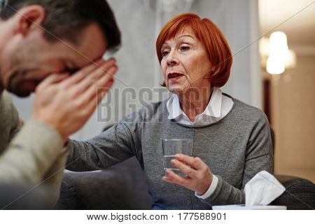 Portrait of pretty mature psychologist trying to comfort her crying middle-aged patient and offering him glass of water, box with paper handkerchiefs standing on table