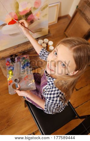 Enjoying my art therapy . Smiling skillful delighted girl sitting in school and having art class while showing her abilities and holding pallet