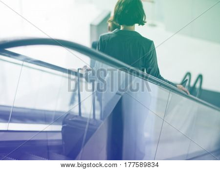 Businesswoman traveling with luggage on escalator