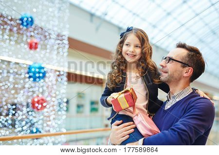 Happy man holding his daughter with gift-box in shopping-center
