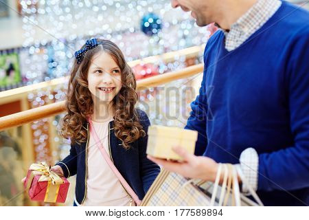 Little girl talking to her father during shopping