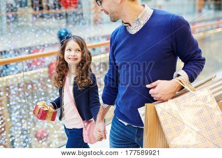 Happy girl with curly hair holding gift-box while walking with her father in the mall