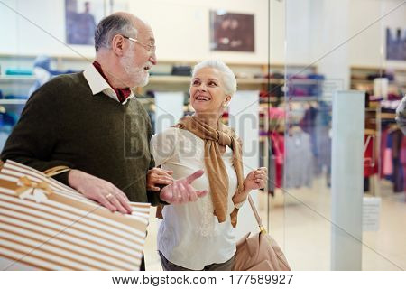 Senior spouses with paperbags talking while shopping in the mall