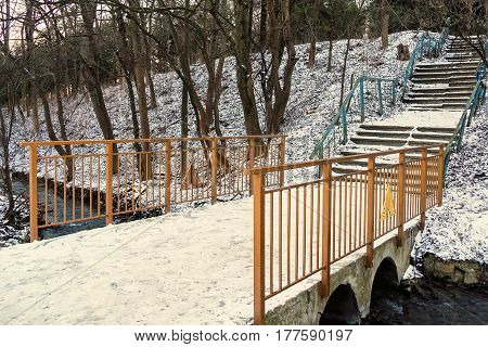 Bridge covered in snow in old abandoned park in winter