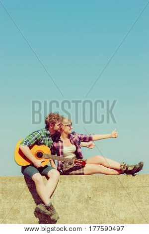Young man playing guitar to his girlfriend outdoor sunny summer day sky background - dating romantic couple