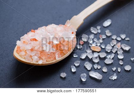 healthy lifestyle pink himalayan salt in a wooden spoon over black background