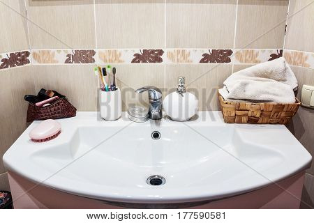 Modern bathroom washbasin with chrome water tap toothbrushes and liquid soap and cosmetics