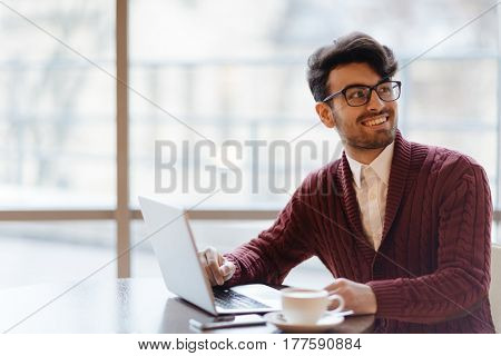 Smiling businessman talking to someone during network