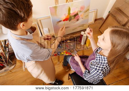 Friendly atmosphere . Helpful smiling delighted kids sitting in school and having art class while demonstrating their skills and painting