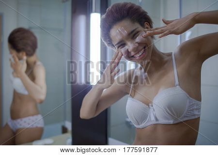 Beautiful Young African Woman Spreading Cream On Her Face And Smiling Standing Against A Mirror In B