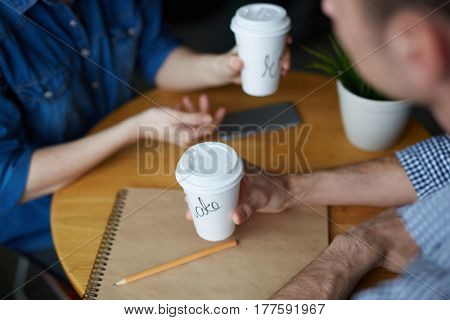 Close-up shot of young HR manager sitting at cafe table, drinking delicious coffee and conducting interview with female applicant for position