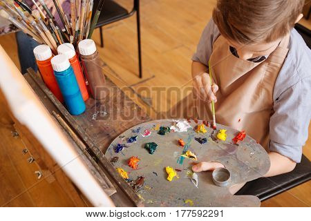 Creating my piece of art. Attentive involved skillful child sitting in the art studio and having pictorial class while holding pallet and mixing colors