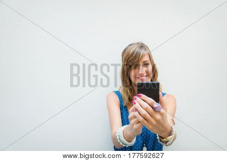 Cute girl using cellphone in front of a white wall - facade.