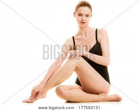Depilation epilation clean fresh skin concept. Woman in black swimsuit underwear sitting on floor showing and touching her legs. Studio shot isolated