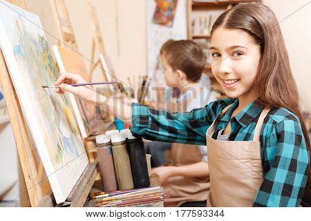 Young gifted generation painting. Energetic ambitious young girl sitting in school and having art class while showing her skills and holding paintbrush