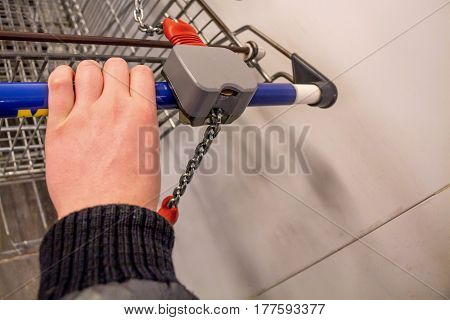 Close-up of hand pushing a trolley in grocery store