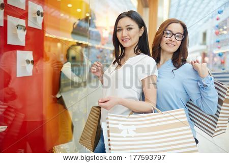 Two young women with paperbags standing by display-window with sunglasses