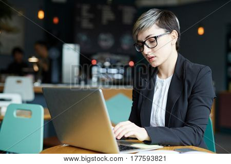 Waist-up portrait of concentrated young businesswoman with stylish haircut sitting at cafe table and writing response letter to her client on laptop