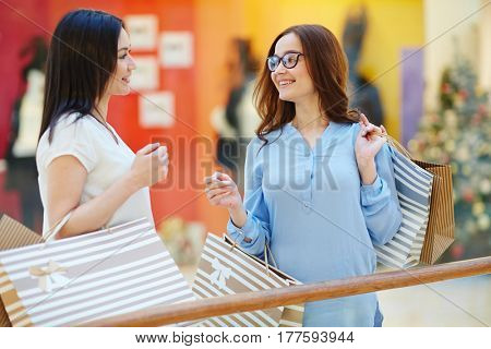 Pretty females talking in the mall during shopping