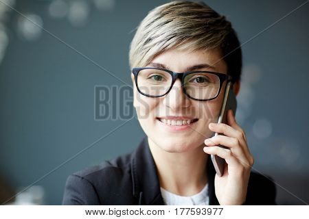 Head and shoulders portrait of smiling businesswoman in stylish eyeglasses looking at camera while calling to her colleague on smartphone