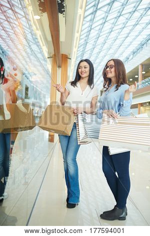 Girls paying attention to display-window during shopping