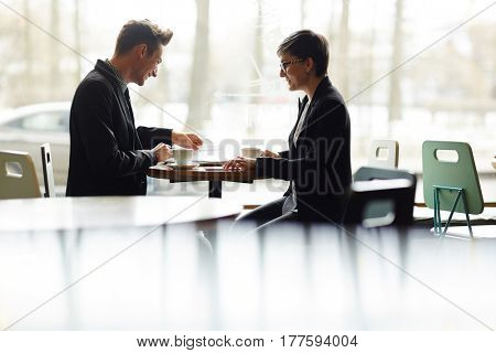 Male and female business partners gathered together in lovely small cafe and having productive meeting, handsome man holding contract in hand