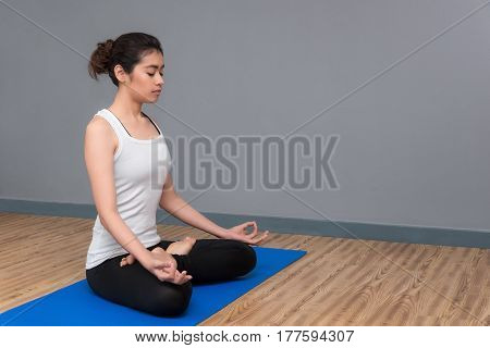 Young Woman Keep Calm And Meditates While Practicing Yoga To At Yoga Sport Gym. Yoga And Meditation