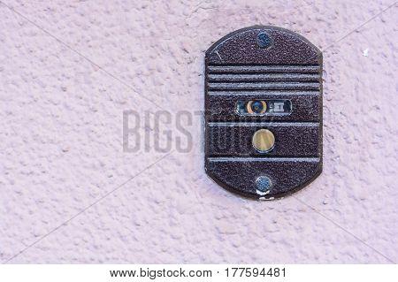 Modern door bell button on grunge plaster surface