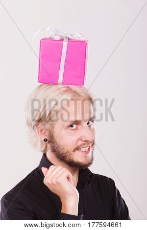 Celebration and happiness concept. Stylish smiling young man with pink gift box on his head. Guy have idea for present