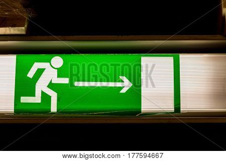 Close up of green emergency exit sign showing the way to escape