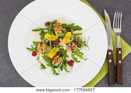 Vegetarian salad with pear, arugula and walnuts. Studio Photo