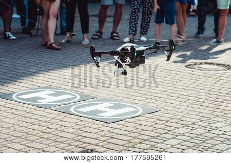 Drone quad copter landing on the helicopter pad. people legs visible who are looking for drones