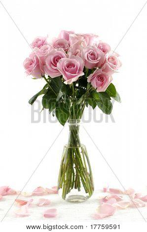 Boeket van roze rozen in een glazen vaas met bloemblaadjes geïsoleerd op wit
