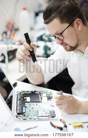 Side view portrait of modern man, wearing glasses,  inspecting disassembled laptop with flashlight, looking for broken pats at table in workshop