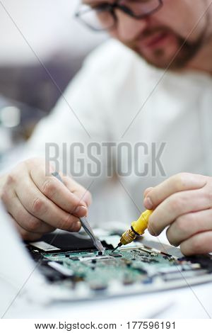 Closeup shot of man in glasses  working on disassembled laptop with screwdriver and tweezers looking for broken pats